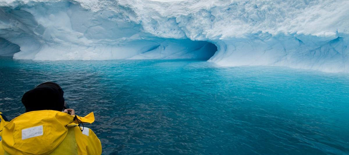 reporter in kayak near glacier