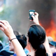 people with cell phones at a fire